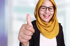 Muslim Businesswoman Showing OK Thumb Up Gesture. Portrait of beautiful muslim businesswoman wearing hijab showing ok thumb up gesture over blurred defocus Stock Photography