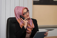 Muslim Businesswoman Talking On Telephone In Office Stock Image