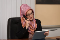 Muslim Businesswoman Talking On Telephone And Using Computer Stock Image