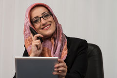 Muslim Businesswoman Talking On Telephone And Using Computer Royalty Free Stock Photos