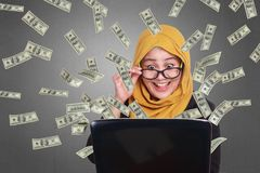 Muslim Businesswoman Working on Laptop with Rain of Money Royalty Free Stock Photo
