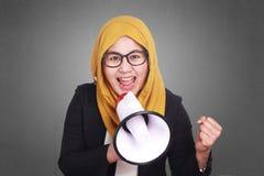 Muslim Businesswoman Yelling Motivating with Megaphone. Portrait of muslim businesswoman leader manager wearing hijab shouting yelling motivating with megaphone Stock Image