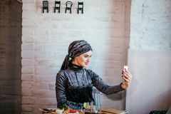 Muslim woman taking selfie in cafe with smartphone Royalty Free Stock Photo
