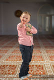 Muslim child holding Koran. In hands in mosque royalty free stock images