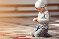 The Muslim child prays in the mosque, the little boy prays to God, Peace and love in the holy month of Ramadan. Royalty Free Stock Photos