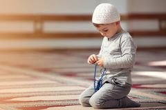 The Muslim child prays in the mosque, the little boy prays to God, Peace and love in the holy month of Ramadan. Stock Photo