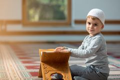 The Muslim child prays in the mosque, the little boy prays to God, Peace and love in the holy month of Ramadan. Royalty Free Stock Photo