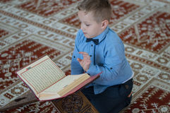 Muslim child reading Koran. In mosque Stock Photo