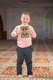 Muslim child reading Koran. In mosque royalty free stock photo