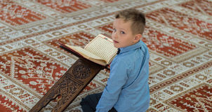 Muslim child reading Koran. Muslim child pray in mosque stock photography