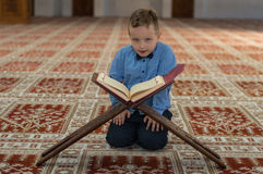 Muslim child reading Koran. Muslim child pray in mosque Royalty Free Stock Photos