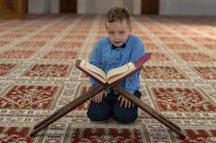 Muslim child reading Koran. Muslim child pray in mosque royalty free stock photos