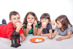 Muslim Children eating Kahk - Kaak ( Cookies ) in the feast. Happy kids celebrating Eid El Fitr - Muslim Children eating Kahk - Kaak ( Cookies ) in the feast Stock Photo