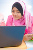 Muslim college girls. Muslim girls. Southeast Asian Muslim college girls discussing, looking on laptop screen, indoor royalty free stock photography