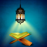 Muslim community Holy Month of Ramadan Kareem. Hanging illuminated arabic lamp and open holy book Quran on blue background for Ramadan Kareem