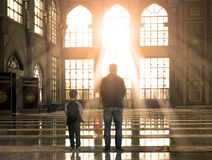 Muslim concept: Muslim father and son are worshipping in worship. Rehabilitation concept: Silhouette a disabled man standing up and raising his crutches at royalty free stock photos
