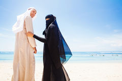 Muslim couple on a beach. Wearing traditional dress stock images