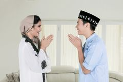 Muslim couple forgiving each other at home. Muslim couple giving greets hand to forgiving each other during Eid Mubarak celebration at home stock photography