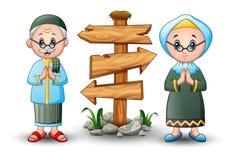 Muslim couple greeting cartoon with blank wood arrow sign Stock Image