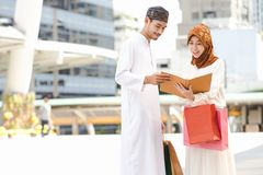 Muslim couple. Young girl and boy reading book with shopping in the city,Concept education and shopping Royalty Free Stock Photo