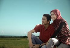 Muslim couple outdoor. Sitting with rice field and ocean at background Stock Images