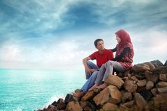 Muslim couple outdoor. Sitting on rock Royalty Free Stock Photos