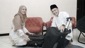 Muslim couple put stuff in suitcase lugage ready for traveling stock photography