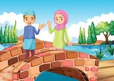 A Muslim couple waving at the bridge Stock Photo