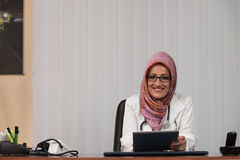 Muslim Doctor On A Break With Her Touchpad Royalty Free Stock Photos
