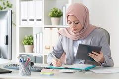 Muslim doctor carrying mobile digital tablet