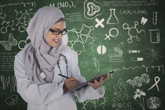 Muslim doctor with clipboard and scribbles Royalty Free Stock Photo