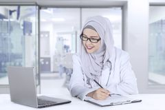 Muslim doctor with a laptop in the hospital. Image of a beautiful female doctor wearing a veil while working in the hospital with a laptop and clipboard on the Royalty Free Stock Images