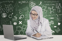 Muslim doctor with scribbles on the chalkboard Royalty Free Stock Photos