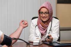 Muslim Doctor Taking Young Man's Blood Pressure Stock Photos