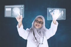 Muslim doctor is working with a futuristic interface Stock Photos