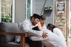 Muslim eid mubarak forgiving others. Family embracing each other during eid mubarak celebration. Forgiving by kneeling and pressing face to another`s knees stock images