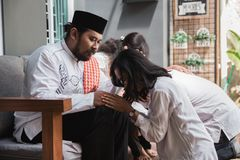 Muslim eid mubarak forgiving others. Family embracing each other during eid mubarak celebration. Forgiving by kneeling and pressing face to another`s knees stock image