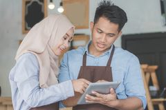 Muslim entrepreneur concept together. Two business partner using tablet in front of their coffee shop. muslim entrepreneur concept Royalty Free Stock Photography
