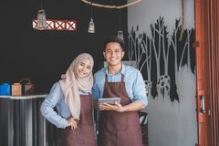 Muslim entrepreneur concept together. Two business partner using tablet in front of their coffee shop. muslim entrepreneur concept Royalty Free Stock Image