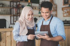 Muslim entrepreneur concept together. Two business partner using tablet in front of their coffee shop. muslim entrepreneur concept Stock Images