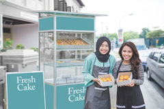 Muslim entrepreneur with partner starting food stall business. Young muslim entrepreneur with her partner starting their business by opening small food stall royalty free stock photo