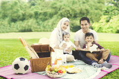Muslim family with a book in the park Royalty Free Stock Images