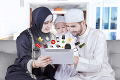 Muslim family buying products online. Happy muslim family sitting on the sofa while shopping online with tablet at home royalty free stock images
