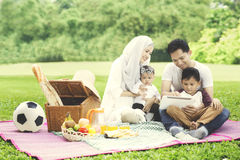Muslim family with digital tablet in the park Royalty Free Stock Photography