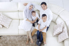 Muslim family enjoying their togetherness. High angle of muslim family enjoying their togetherness while sitting on the sofa Stock Photos