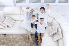 Muslim family expressing their happiness. Top view of muslim family expressing their happiness while sitting on the sofa together stock image