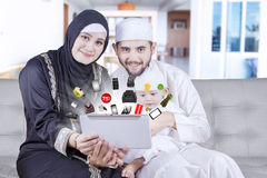 Muslim family hold tablet for shopping online. Happy muslim family sitting on the couch while holding a digital tablet for shopping online at home stock images