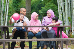 Muslim family lifestyle. Happy Southeast Asian family sitting at garden bench chatting with each other, outdoor lifestyle at nature green park stock images