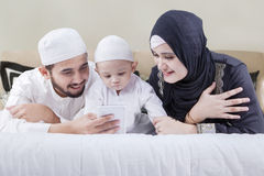 Muslim family lying on bed with smartphone. Portrait of muslim family lying on the bed while watching video on a smartphone Royalty Free Stock Image