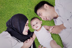 Muslim family lying down on grass Stock Images